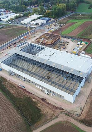 8.200 m² Element-Dach mit Akustik-Kassette, 3.450 m² Kassetten, 4.370 m² Planum-Fassade (Halle) in RAL 9010; Fassade und Untersicht Büro 1.520 m² Planum-Fassade Alu in RAL 9010
